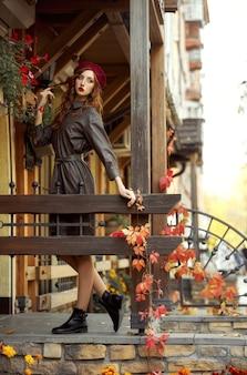Осенью на крыльце стоит модная рыжая женщина в бордовом берете и кожаном плаще.