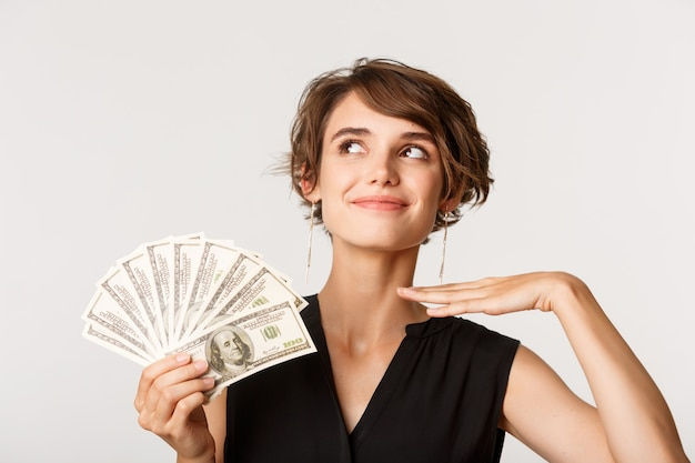 Fashionable rich elegant woman looking sassy, showing money, standing over white.