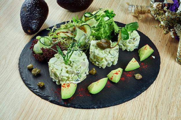Модный русский салат оливье с авокадо и креветками на черной грифельной доске. крупным планом вид на вкусный салат из морепродуктов