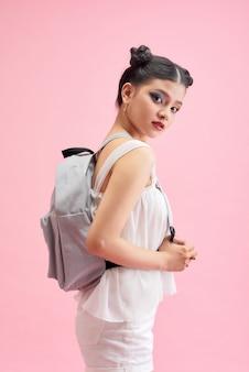 Модная школьница держит рюкзак за плечами и смотрит прямо в камеру, изолированную на сияющем розовом фоне