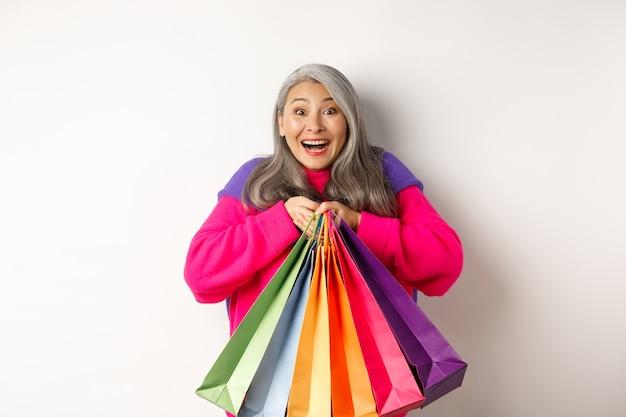 買い物中毒のファッショナブルなシニアアジアの女性、買い物袋を抱き締めて、うれしそうな笑顔、割引で購入、白い背景の上に立って