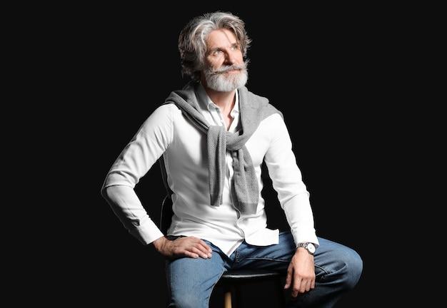 Модный старший мужчина, сидящий на стуле