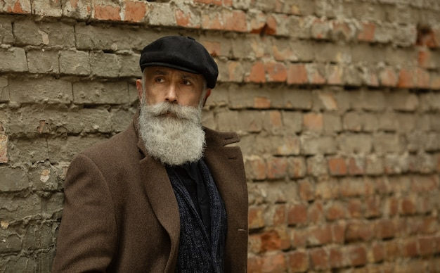 Fashionable senior man with gray hair and beard is outdoors on the street.