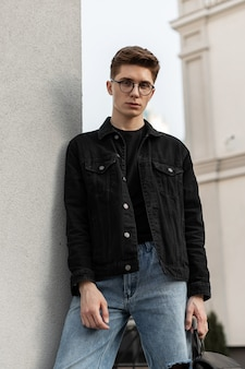 도시의 벽 근처에 쉬고 배낭 빈티지 안경에 세련 된 청바지 청소년 캐주얼 착용 유행 심각한 젊은 남자 패션 모델. 야외 도시 유행 남자. 봄 컬렉션 남성복