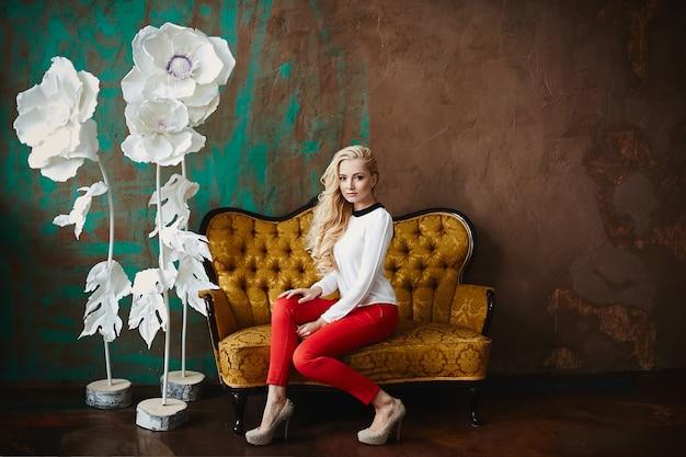 Модная, сексуальная и красивая блондинка модель девушка, в блузке и красных штанах, позирует на диване на роскошном фоне.