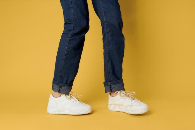 ファッショナブルな靴白いスニーカー脚黄色の背景トリミングビュー