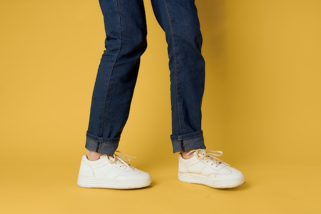 Fashionable shoes white sneakers legs yellow background cropped view