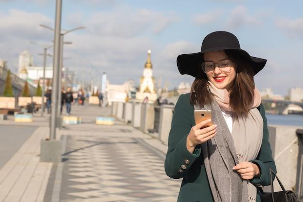 携帯電話でメッセージを入力するスタイリッシュなアパレルに身を包んだメガネでファッショナブルな笑顔のブルネットの女性