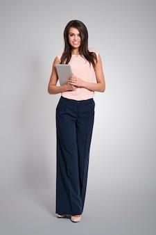 Donna d'affari alla moda e sorridente con tavoletta digitale
