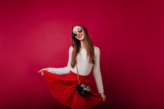 彼女の赤いスカートで遊ぶファッショナブルな笑顔の女の子