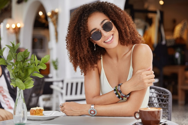 Fashionable smiling pleased african american female in trendy sunglasses, drinks coffee or latte, eats sweet cake, enjoys spare time in cafe