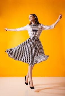 スタジオでポーズをとる美しいドレスを着たファッショナブルな笑顔の女性、黄色のモーションショット