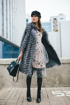 Fashionable smiling woman walking in city in warm fur coat, winter season, cold weather, wearing black cap, dress, boots, holding leather bag, street fashion trend