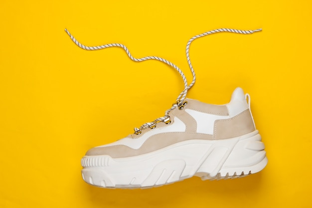 Fashionable sneaker with high soles platform on yellow