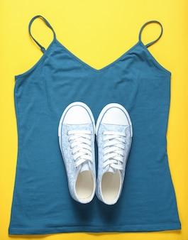Модные кеды лежат на футболке на желтом, вид сверху