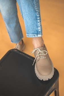 Fashionable sneakers shoes on women feet in denim clothes. lifestyle and trendy design background photo