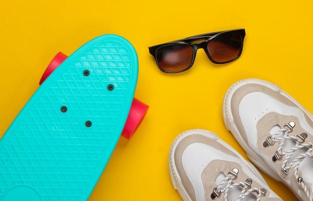 クルーザーボード付きのファッショナブルなスニーカー、黄色のサングラス。若者の楽しみ