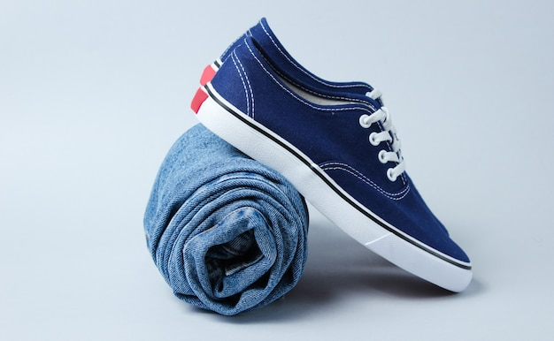 Fashionable sneakers with rolled jeans on a gray table.