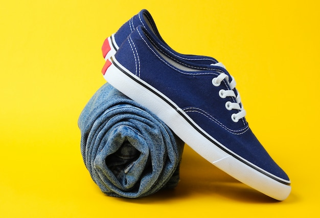 Fashionable sneakers with rolled jeans on yellow table.