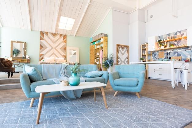 Модная просторная квартира со стильным дизайном в зеленых, серых и белых пастельных тонах с большим окном и декоративными стенами. спальня и кухня