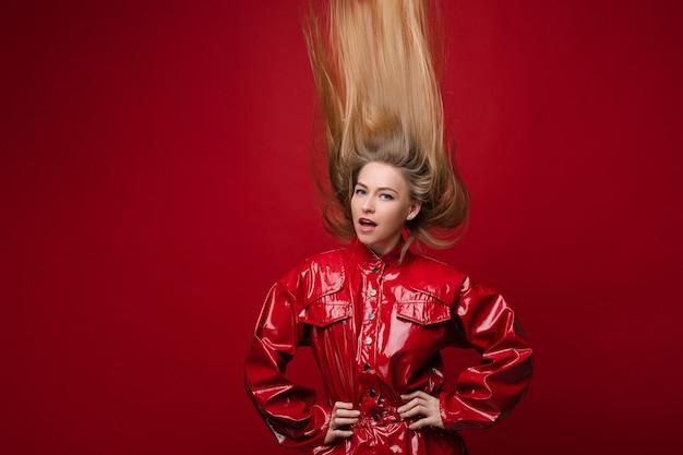 Модное фото стильной блондинки в красном кожаном комбинезоне или комбинезоне с поднятыми вверх ногами волосами. изолированные на ярко-красном фоне.