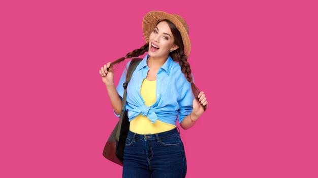 Модная девушка студента в повседневных нарядах и соломенной крышке смеется и держит косички в руках на розовом изолированном фоне. путешественница или турист