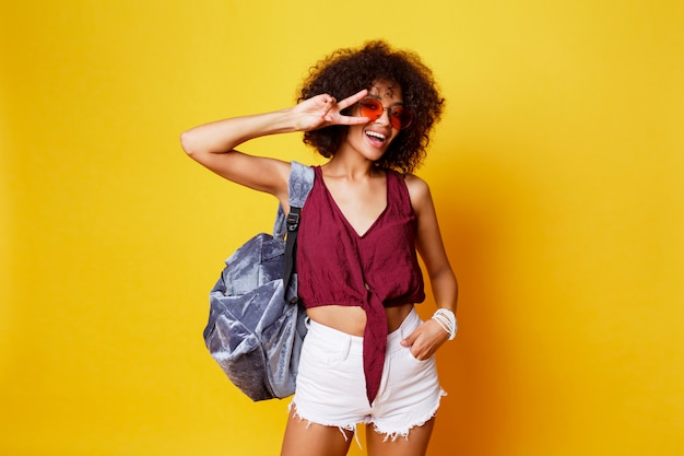 Fashionable studio image of sexy graceful black female with afro hairs. summer outfit, back pack and sunglasses.  lovely woman  dancing  on yellow background.