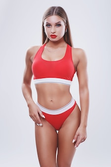 Fashionable studio portrait of a sport girl in red lingerie