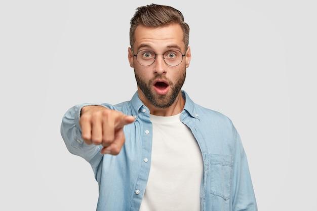剛毛、スタイリッシュなヘアカット、デニムジャケットを着たファッショナブルな唖然とした男性は、驚きの表情であなたを指さし、白い壁に隔離された何かを選択します。 omgと反応の概念。