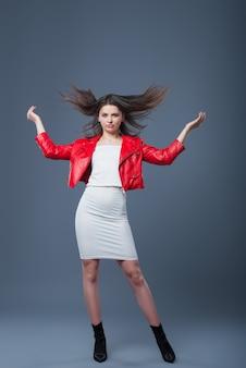 おしゃれなスタイル、ファッションの婦人服、色の組み合わせ。白いドレスと赤い革のジャケットの美しいブルネットの少女。飛んでいる髪。