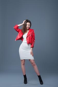유행 스타일, 패션 여성 의류, 색상 조합. 흰 드레스와 빨간 가죽 자 켓 절연 회색 배경에서 아름 다운 갈색 머리 소녀.