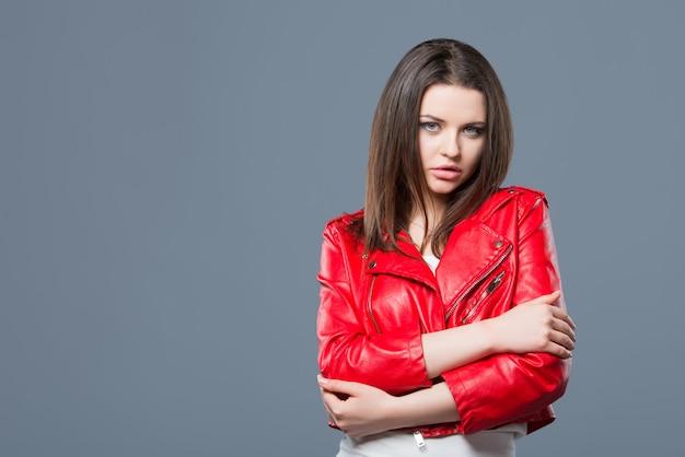 おしゃれなスタイル、ファッションの婦人服、色の組み合わせ。白いドレスと赤い革のジャケットの美しいブルネットの少女は灰色の背景を分離しました。