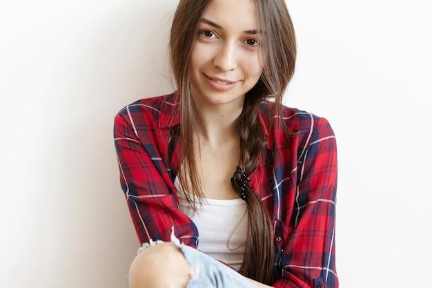 ボロボロになったジーンズと白の上の赤いチェックシャツに身を包んだファッショナブルなスタイリッシュなかわいい若い女性
