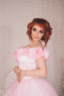 Fashionable stylish portrait of a woman with red short hair. model in pink dress with flowers