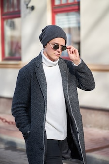 Fashionable stylish young attractive hipster man in sunglasses wearing a gray coat, white sweater and black jeans walking in the street