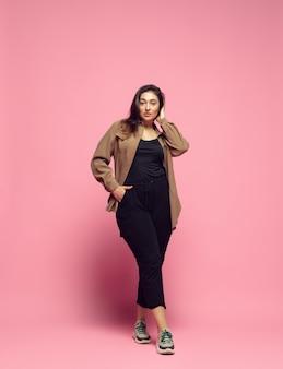 세련되고 세련된. 분홍색 배경에 평상복을 입은 젊은 여성. bodypositive 성격, 페미니즘, 자신을 사랑하는 것, 아름다움 개념. 플러스 사이즈 사업가, 아름다운 소녀. 포용, 다양성.