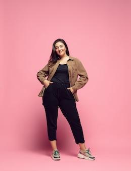 세련되고 세련된. 분홍색 배경에 평상복을 입은 젊은 여성. bodypositive 성격, 페미니즘, 자신을 사랑하는 것, 아름다움 개념. 플러스 사이즈 사업가, 아름다운 소녀. 포용성, 다양성.