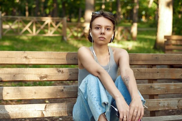 公園のベンチに座って有線ヘッドフォンで音楽を聴くファッショナブルでスタイリッシュな若い女性。