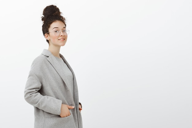 灰色のコートとメガネを着たファッショナブルな成功した女性起業家、ポケットに手を入れて半回転して立って、フレンドリーな笑顔