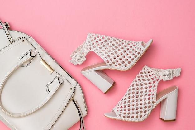 ピンクの背景にファッショナブルな夏の編みこみの靴とバッグ。女性のためのファッショナブルな服やアクセサリー。フラットレイ。
