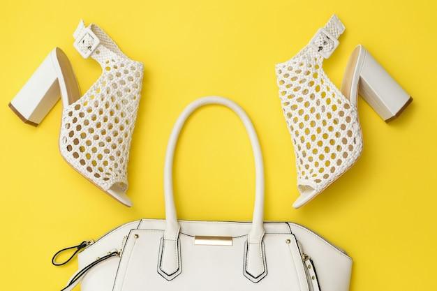黄色の背景にファッショナブルな夏の編みこみの靴とバッグ。女性のためのファッショナブルな服やアクセサリー。フラットレイ。