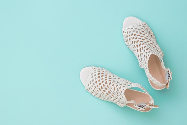 Fashionable summer shoes made of white genuine leather on a blue surface