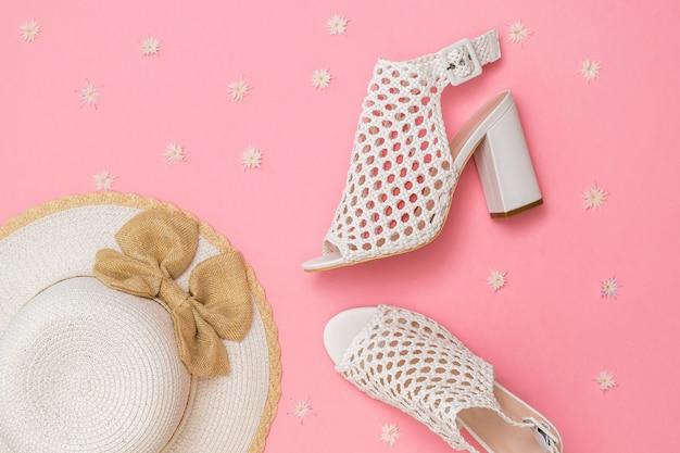 花とピンクの背景に帽子とファッショナブルな夏の靴。女性のための夏の靴。フラットレイ。上からの眺め。