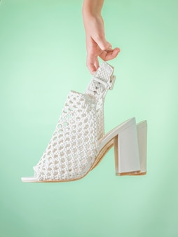 Fashionable summer women's shoes white in the hand of a child on a green background. summer leather shoes for women.