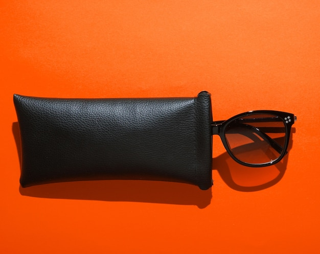 Fashionable sunglasses in protective case on orange background. top view
