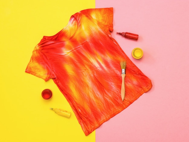 Fashionable t-shirt in the style of tie dye with paints and brushes on a colored surface. staining fabric in tie dye style. flat lay.