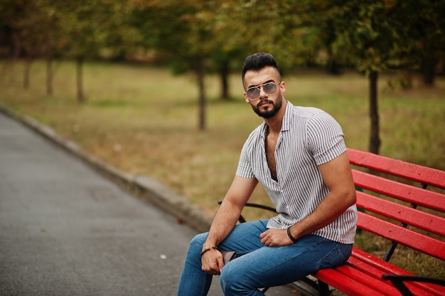 Fashionable tall arab bearded man wears on shirt, jeans and sunglasses sitting on red bench at park