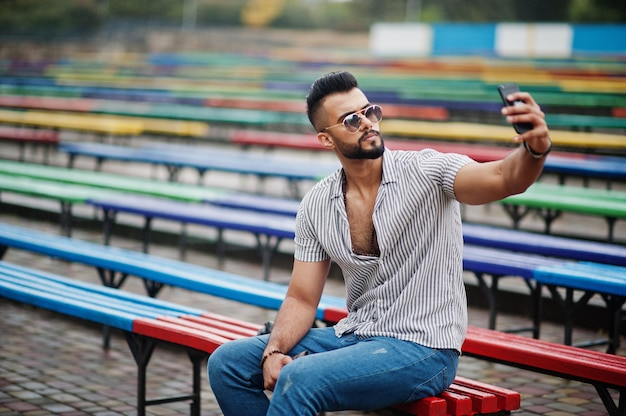 Fashionable tall bearded man wearing shirt, jeans and sunglasses sitting on colored row of benches and use his phone