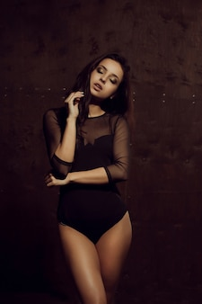 Fashionable tanned brunette woman with sporty body and long hair posing in black lingerie. shadow and light