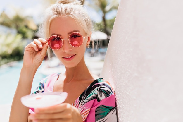 Fashionable tanned woman touching her pink sunglasses